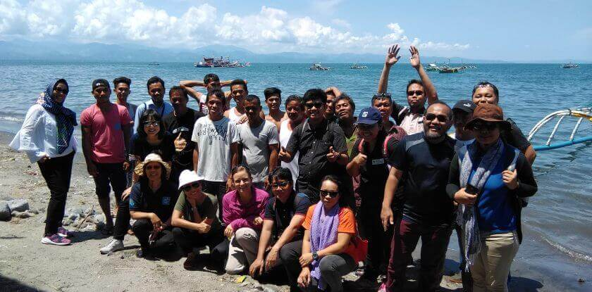 USAID Oceans and small-scale fisher partners gather in a fishing community